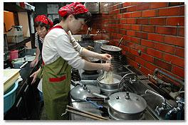 調理場で丁寧に麺を茹がく女将さん